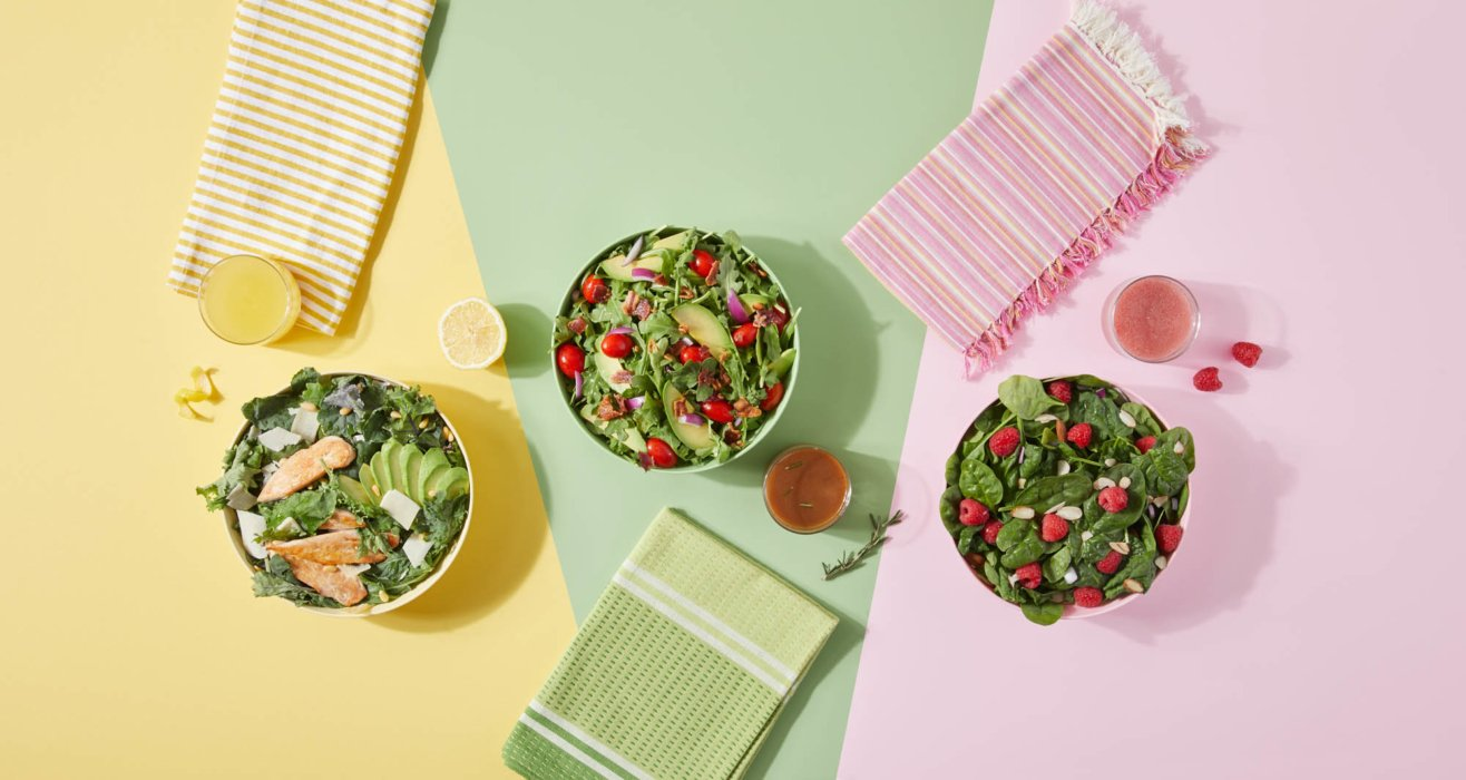 Three beautiful salads on pink green and yellow backgroundsA man walking with equipment - food photography