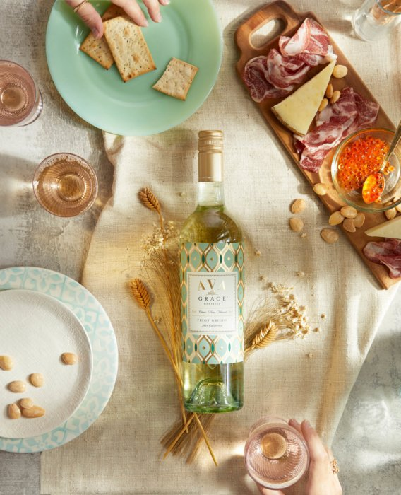 A wine bottle in the middle of beautiful spread charcuterie - Drink Photography