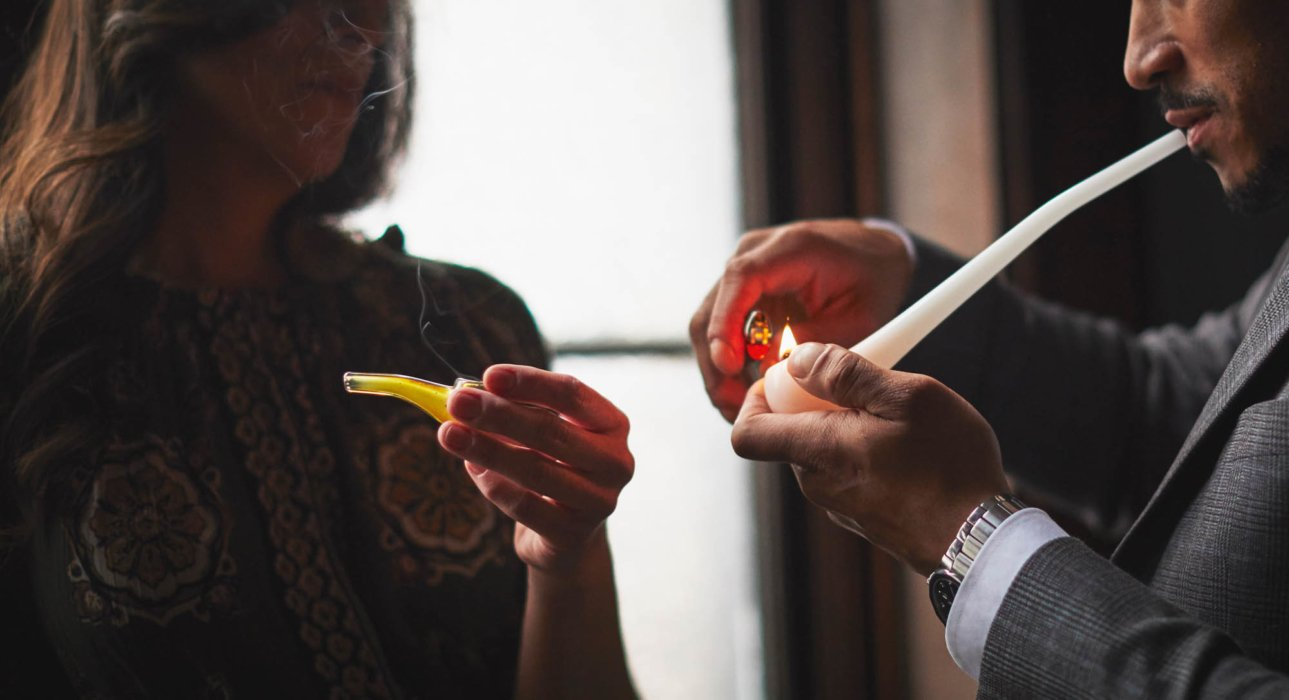 Two people with pipe lighting it up cannabis photgraphy