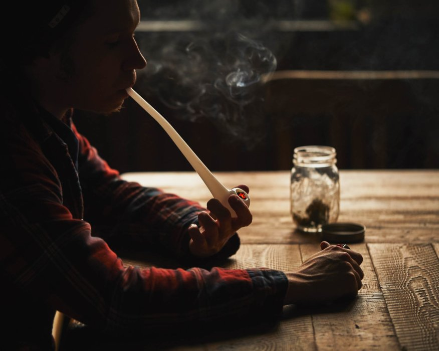 Man sitting down smoking a pipe of weed cannabis photography