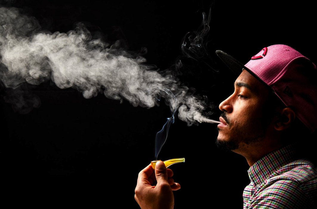 Man with red hate smoking yellow pipe with smokes coming up cannabis photography