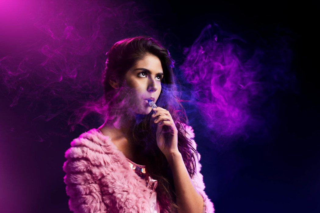 purple light shinning on woman with pink sweater vaping cannabis photography