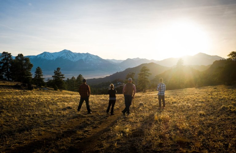 four campers hiking in a mountain range in colorado