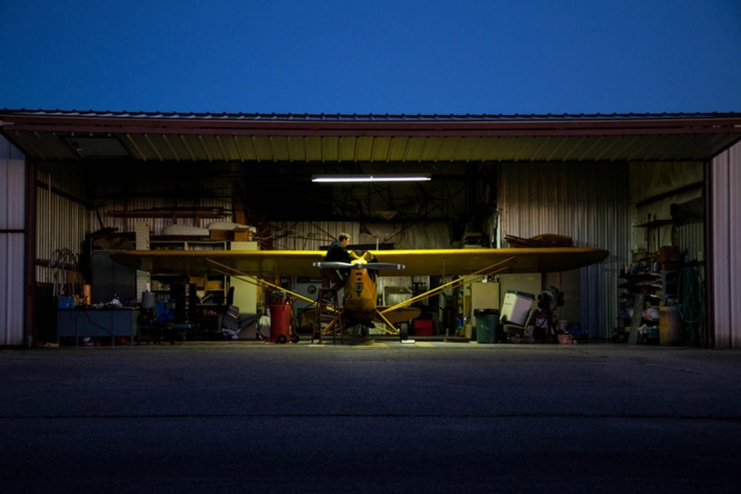 A man working on a small yellow prop plane in a hanger