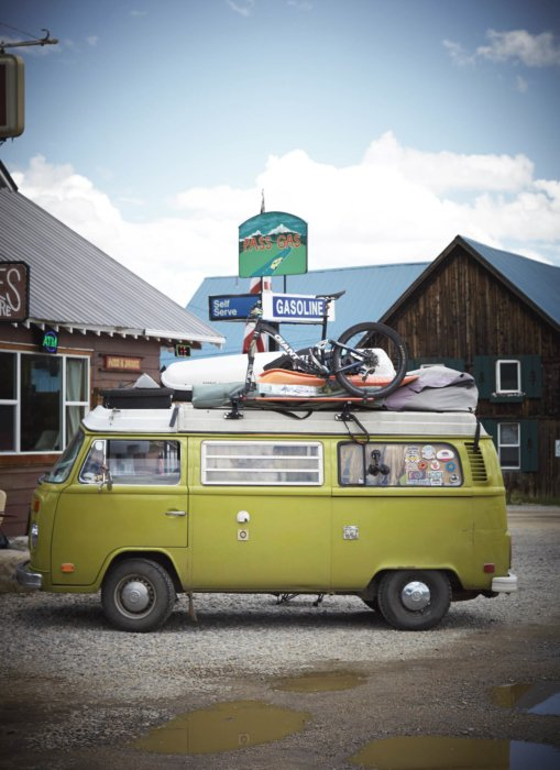 A volkswagen bus van vintage green - loaded with camping gear