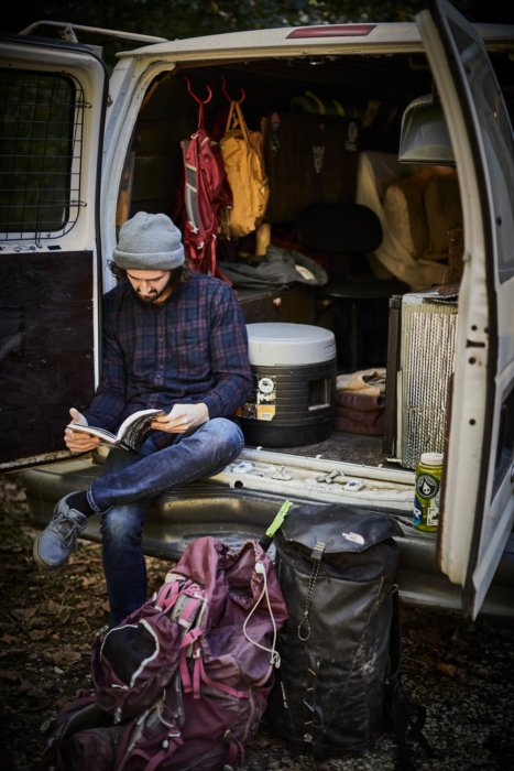A man in the back of his camping van reading a book getting ready for a rock climb