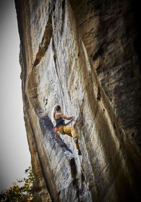 A woman rock climber climbing a rock wall in the red river gorge