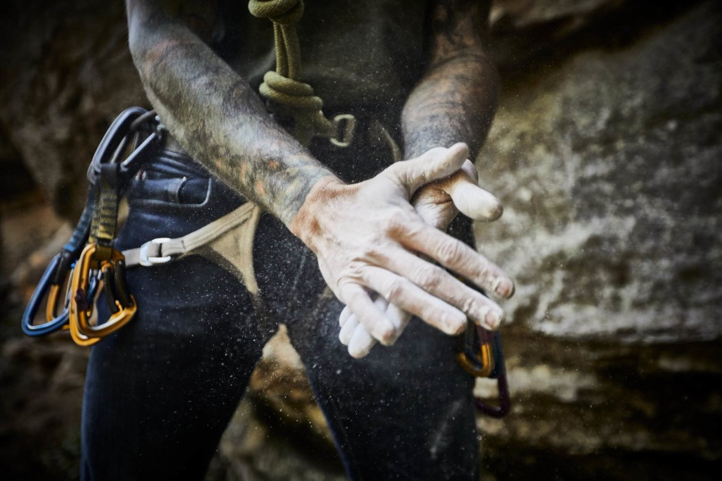 A rock climber clapping with chalk in his hands