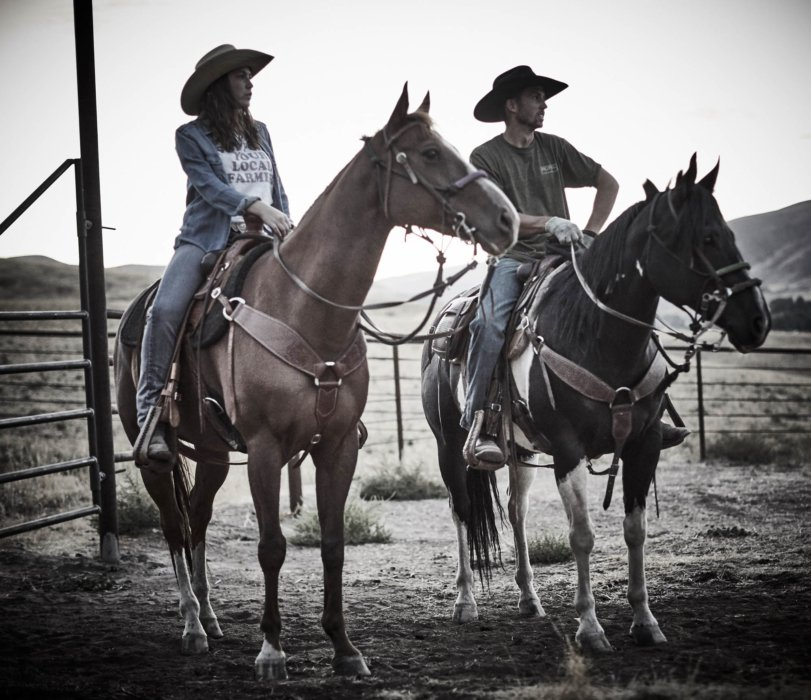 Two ranchers riding their horses on a ranch ready for a ride