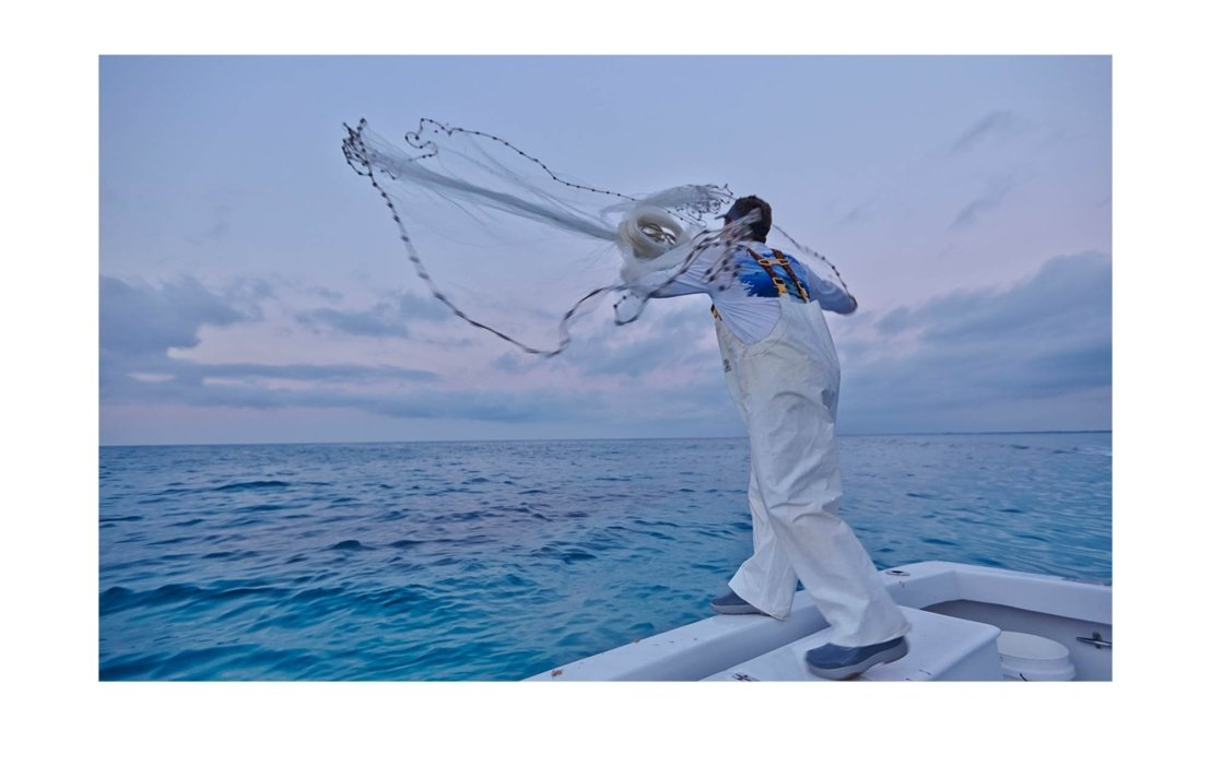A fisherman with a net throwing them into the water