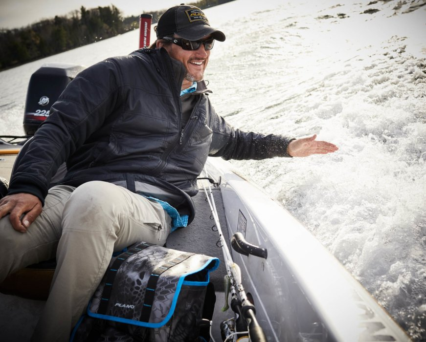 A fisherman outdoors enjoying riding on a boat with plano gear