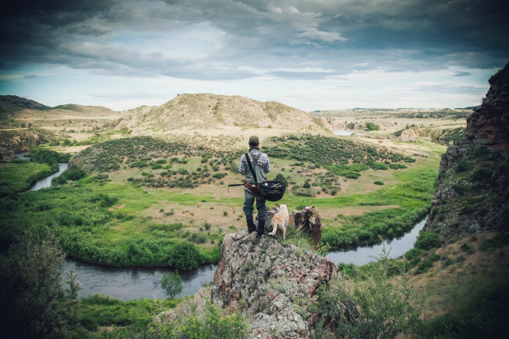 A man and his dog up in the mountains above a fishing stream