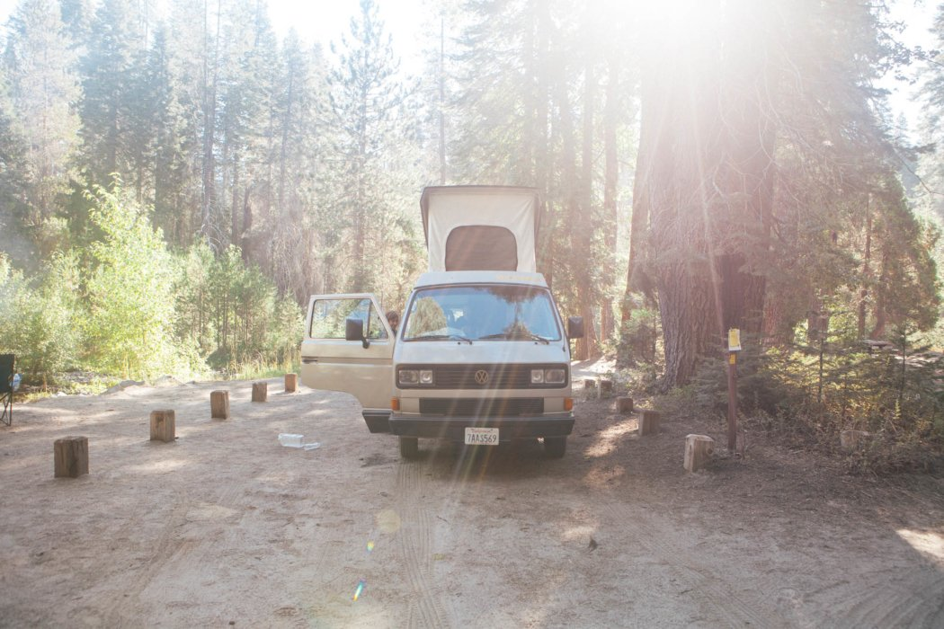 A Volkswagen van and camper at a camp site