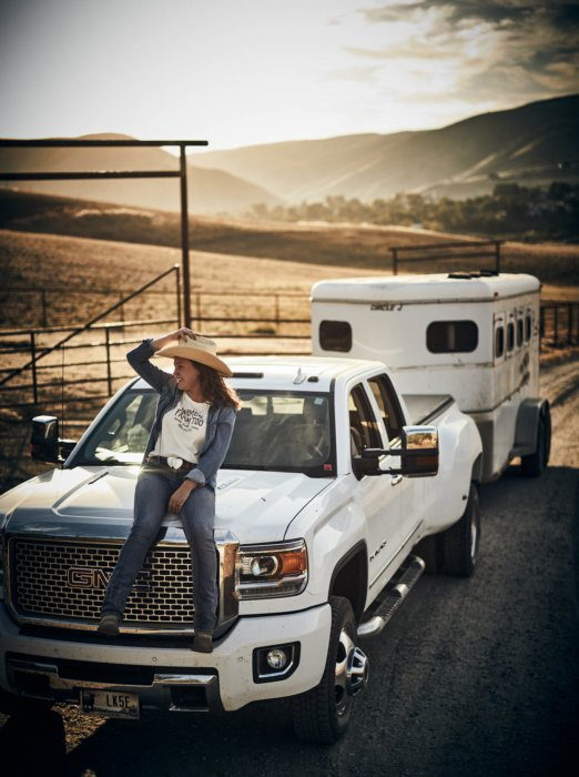 A woman rancher sitting on the hood of her GMC truck with Horse trailer