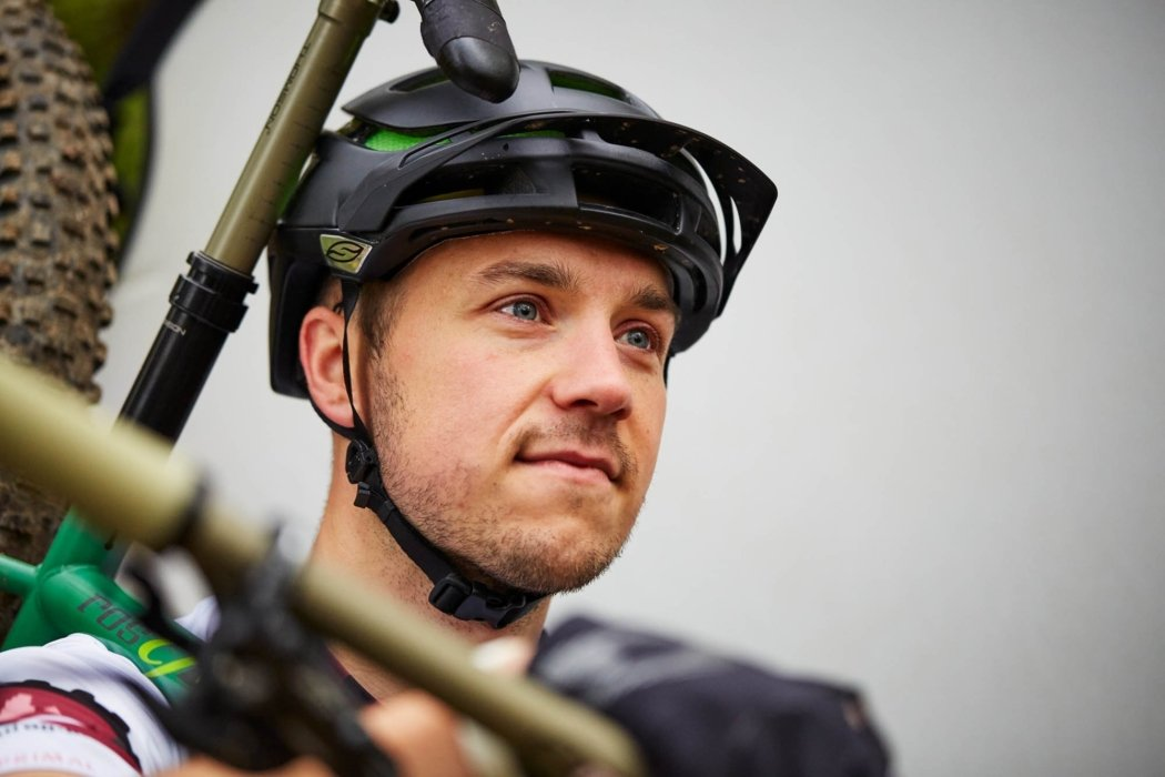 A cyclist portrait carrying his bike