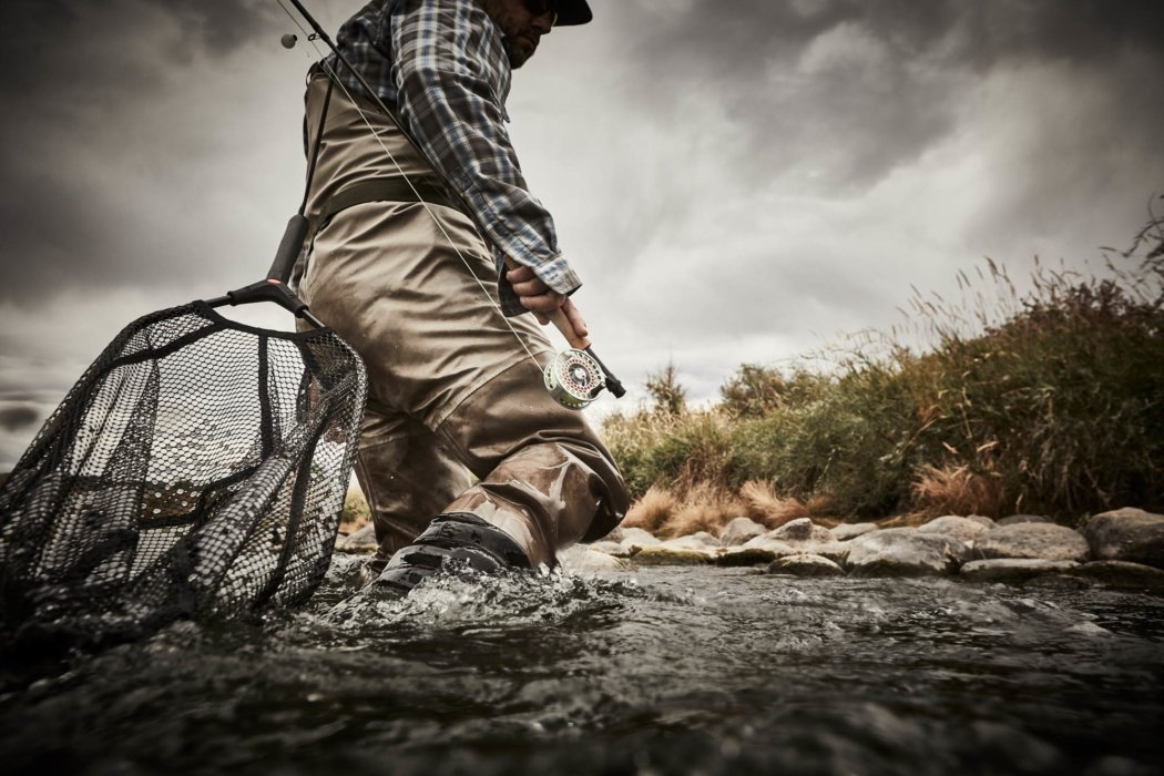 A fisherman with a fly rod wading through the water