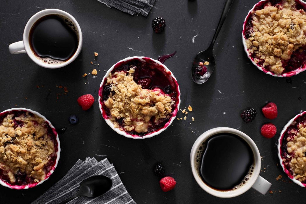 A beautiful raspberry black berries crumble with hot cups of coffee