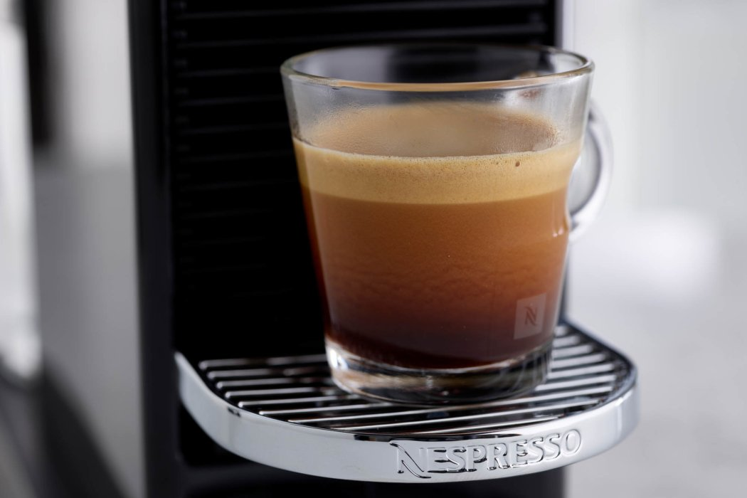 Nespresso coffee filling a small glass cup