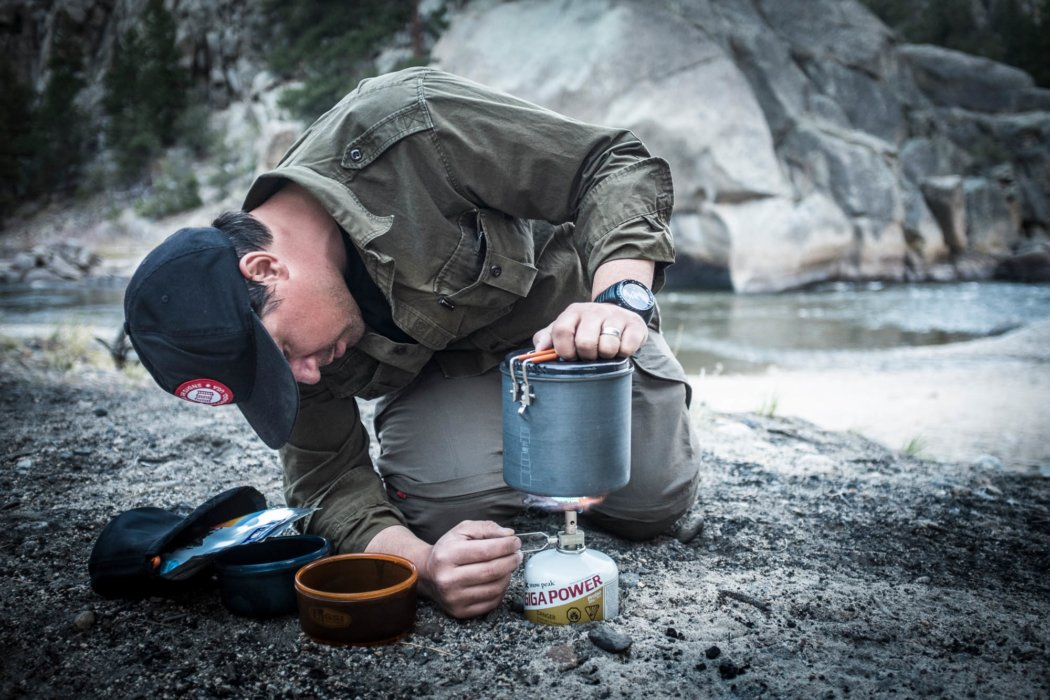 A man setting up a camping burner for cooking