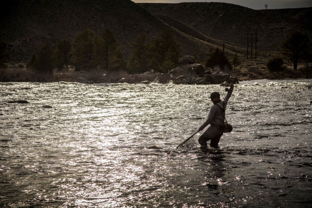 A person fly fishing in a rolling moutain stream