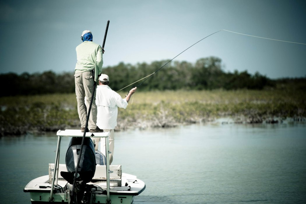 A fly fisherman casting on a boat in brackish water