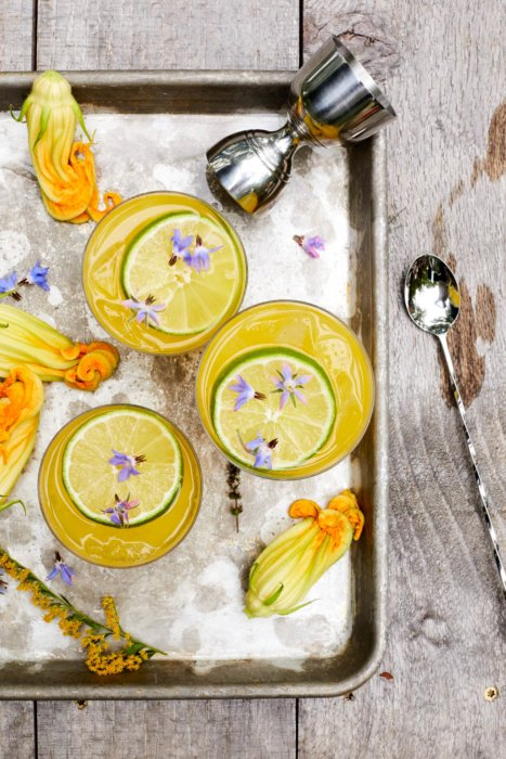Farm to table cocktails on a tray with zucchini flowers