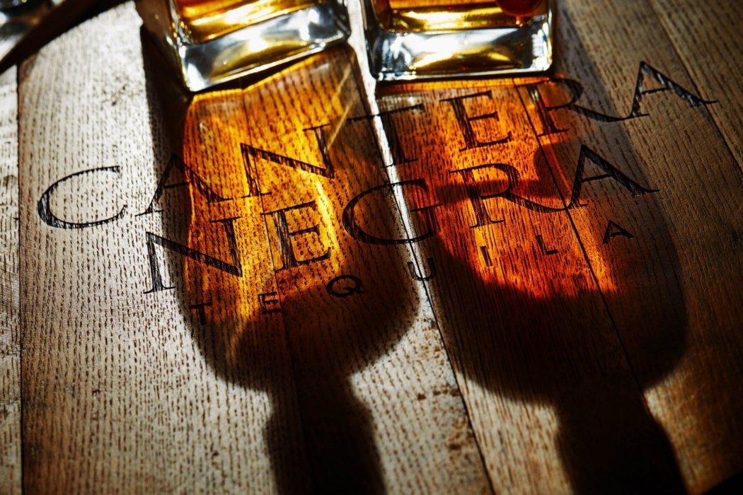 A sparkling shot of Cantera Negra tequila on wooden barrel.