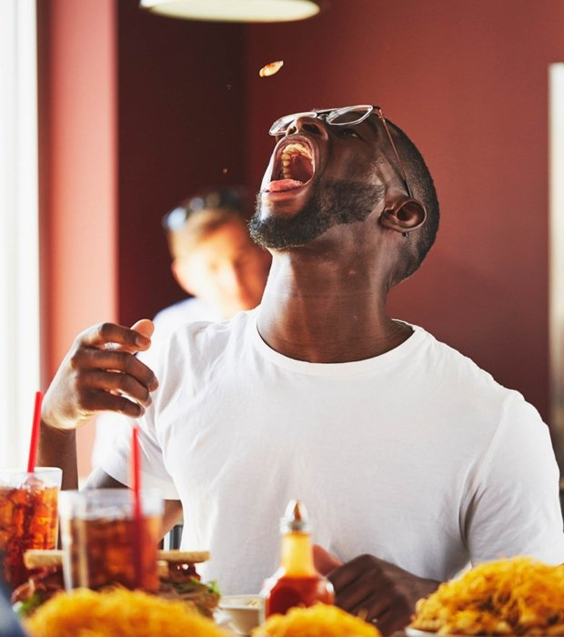 man with glass catching fresh food from his mouth in a restaurant