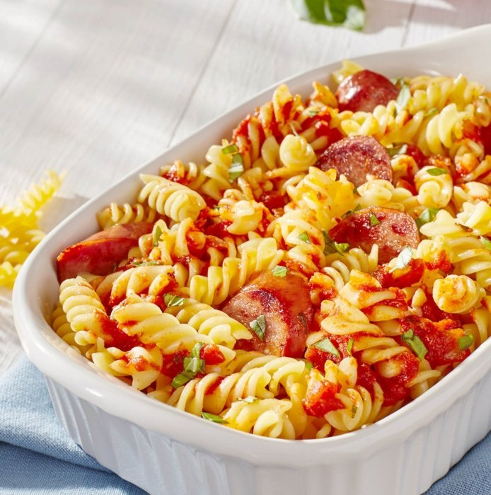 White ceramic bowl with spiral noodle and fresh red sauce and cut meat