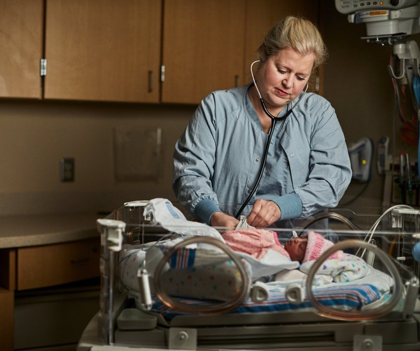 nurse listening to newborn girl in healthcare