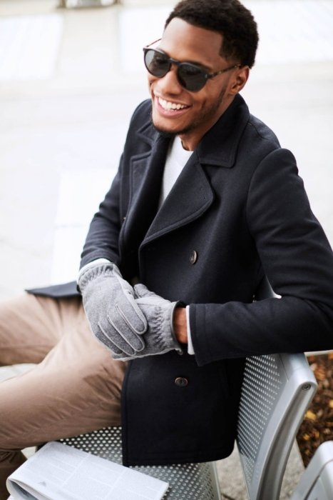 Young man on a metal bench wearing gray gloves and a black sunglasses smiling