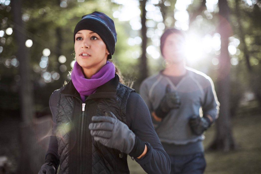 Two people outside in the woods running with their warm work out clothes with gloves