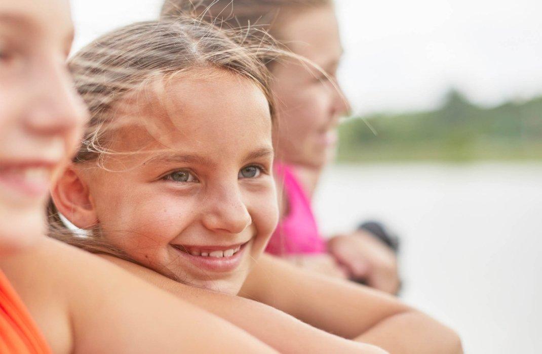 three little girl outside smiling