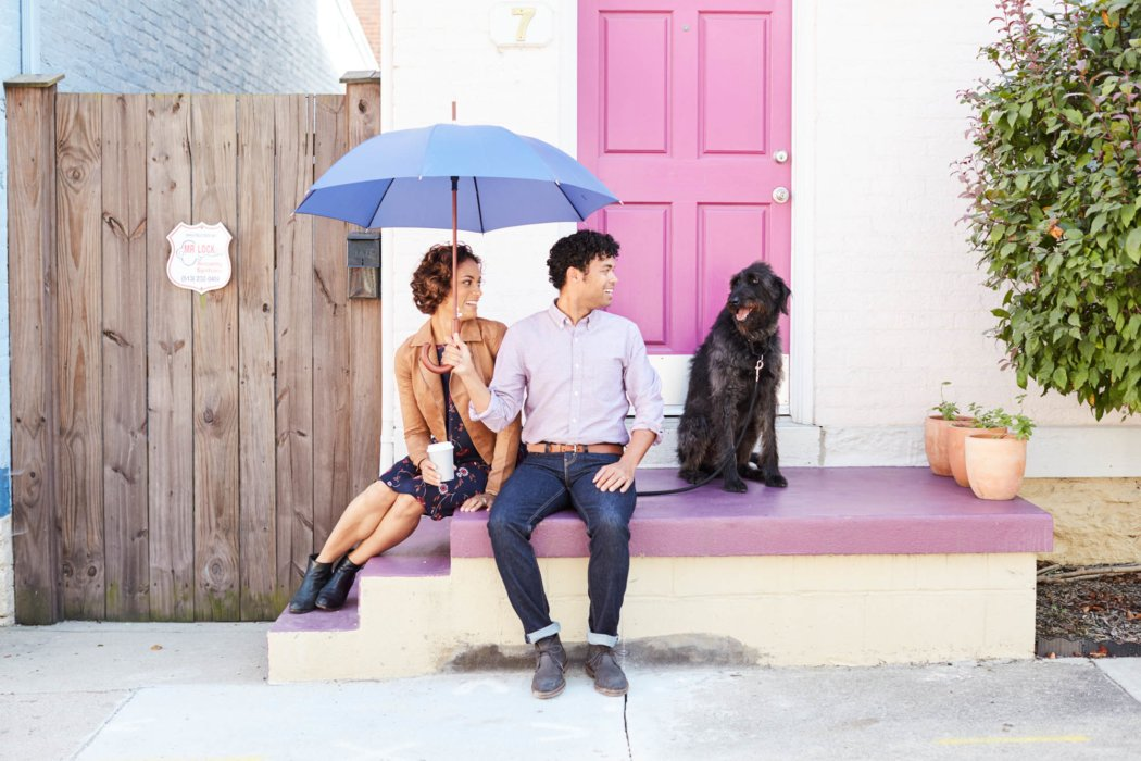 couple sitting on the front purpl porch holding blue umbrella looking at a black dog