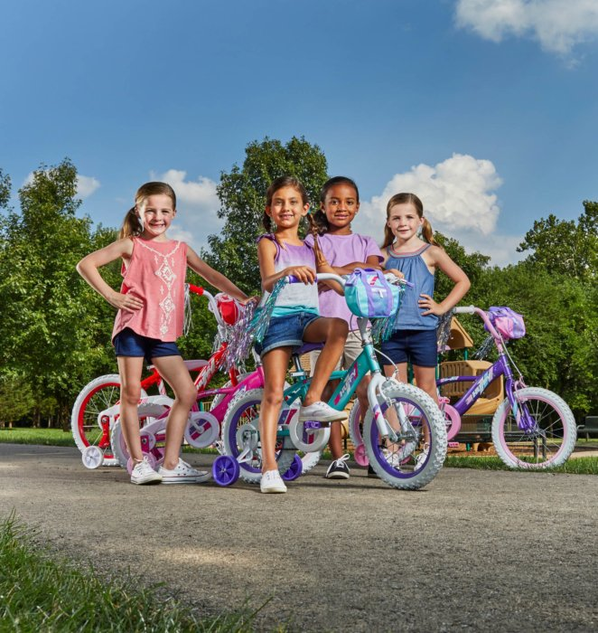 group of four little girls with their training wheels bikes all smiling