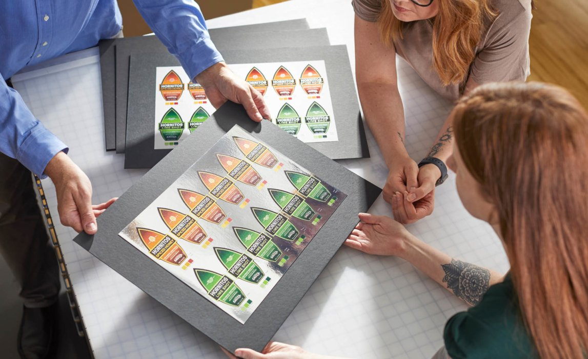 A group of people looking at prototype labels in a meeting