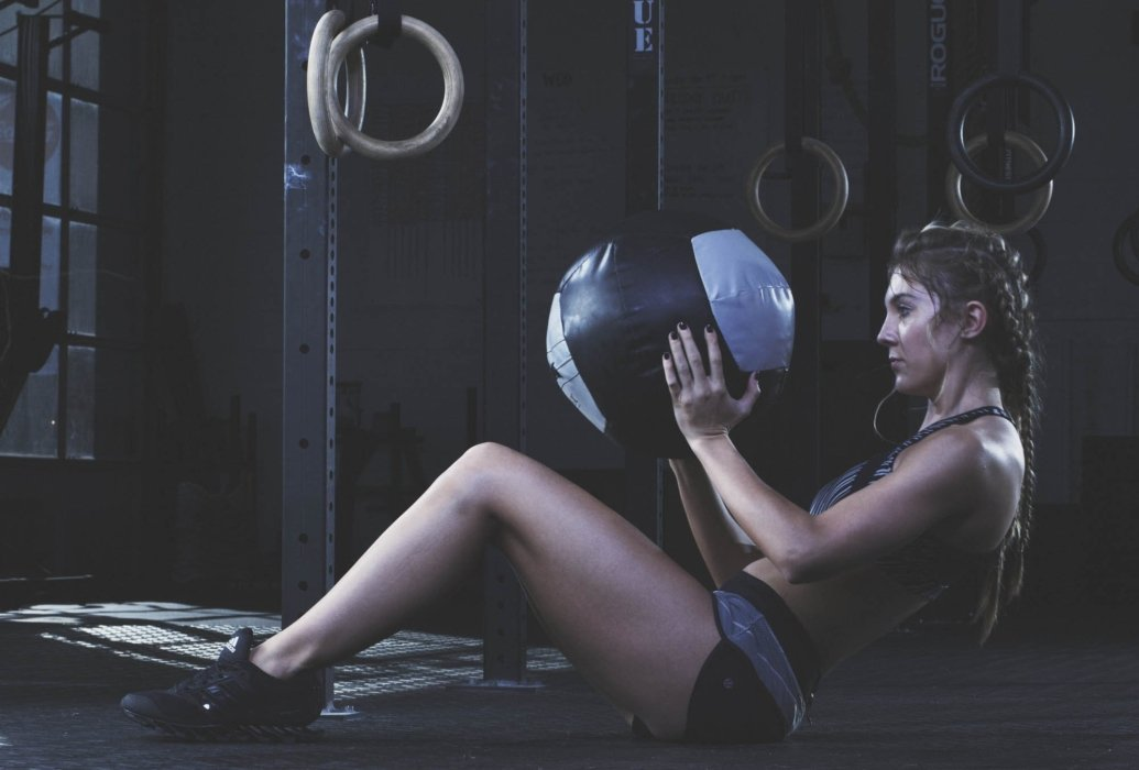 A young woman training with a medicine ball