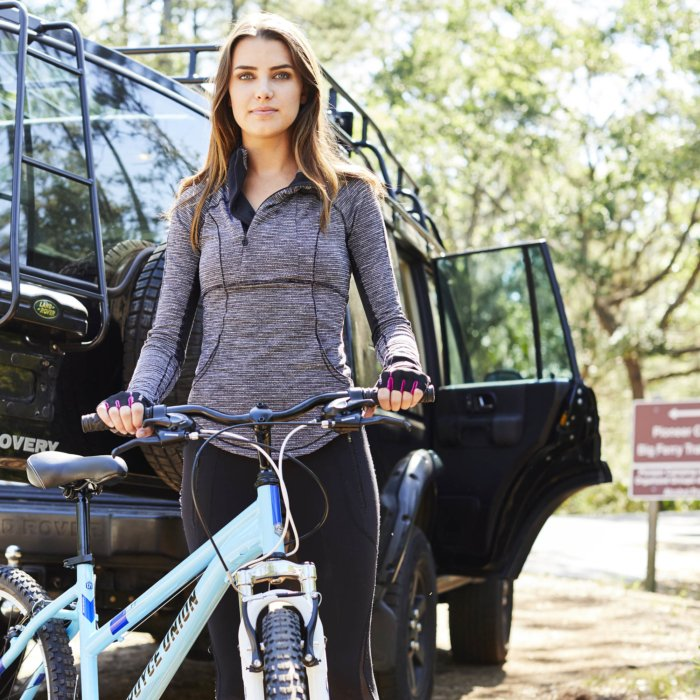 A female cyclist standing next to her bike