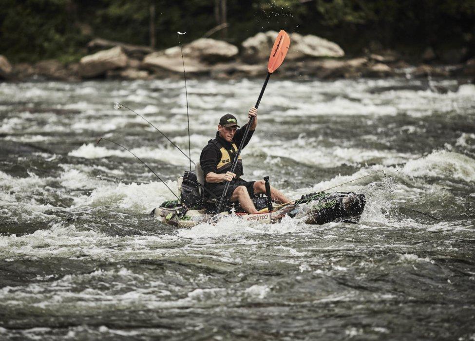A man rowing a kayak down a treacherous river