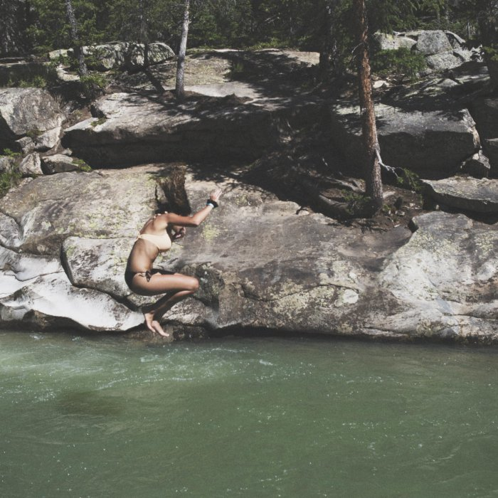 a young woman jumping into a calm green river pool