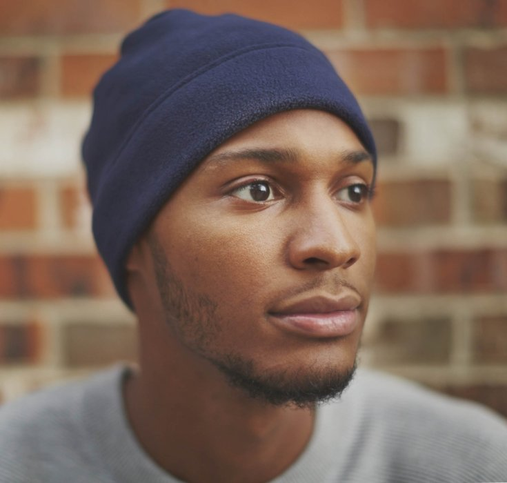 A man wearing a hat in an urban brick setting lifestyle