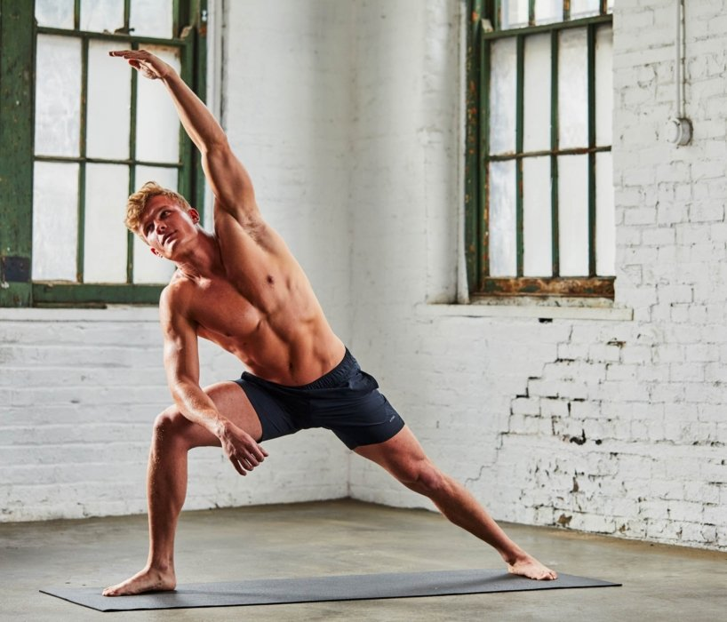 A man stretching in an urban warehouse for yoga class and mat
