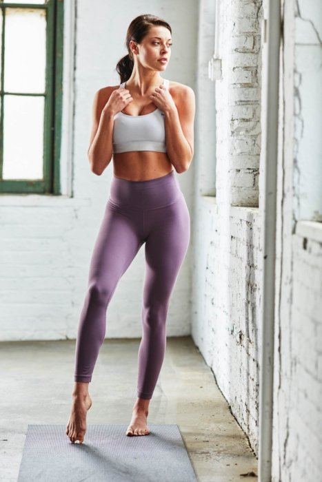 A woman wearing a sports bra and yoga pants getting ready for yoga in an urban setting