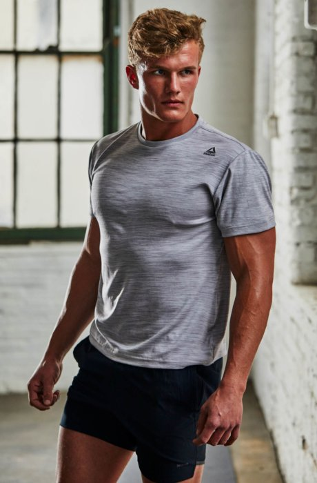 A man wearing active apparel in an urban warehouse setting