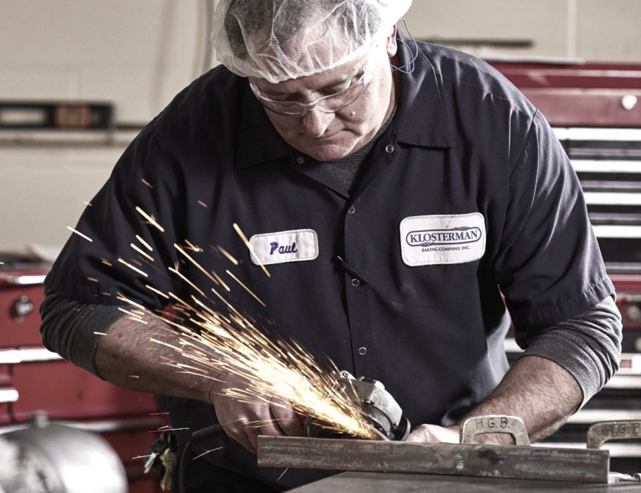 A male repairman grinding metal in a industrial workplace