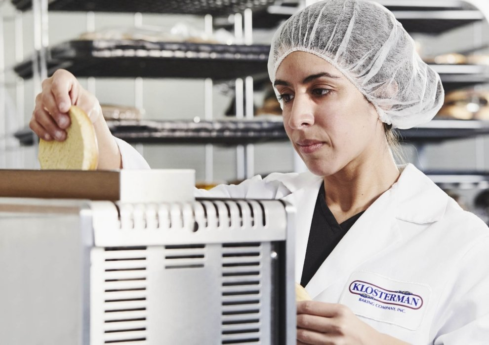 a woman inspecting buns in an industrial bakery workplace