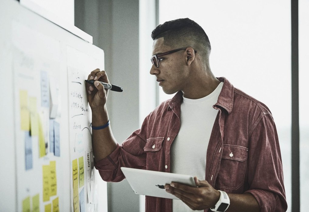 A man writing on a whiteboard in a corporate workplace meeting