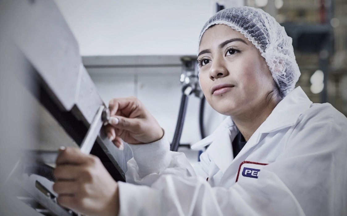 A young woman line worker in an industrial plant workplace
