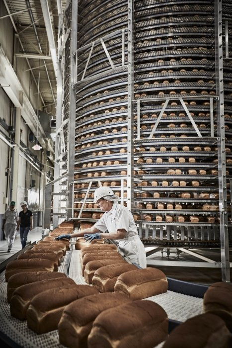 A worker in an industrial bread factory - work photography