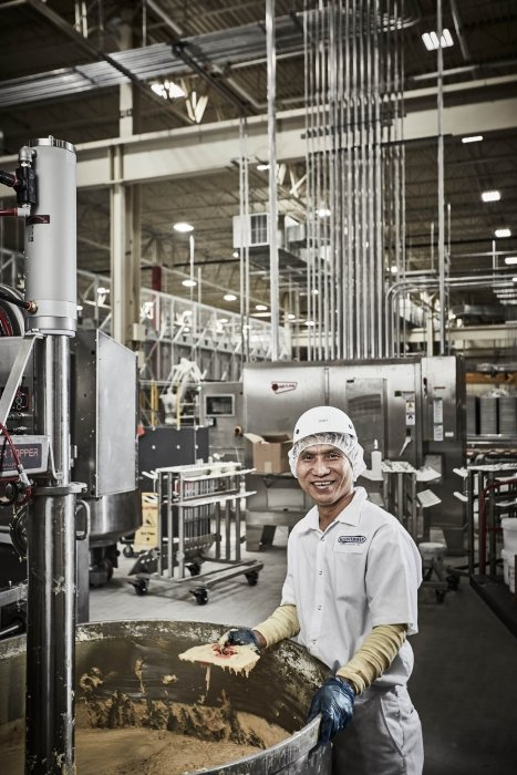 A man smiling working in a industrial - work photography
